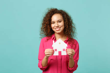 Portrait of smiling african girl in pink casual clothes holding in hand paper house isolated on blue turquoise wall background in studio. People sincere emotions lifestyle concept. Mock up copy space