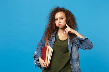 Young african american girl teen student in denim clothes, backpack hold books isolated on blue background studio portrait. Education in high school university college concept. Mock up copy space Stock Photo