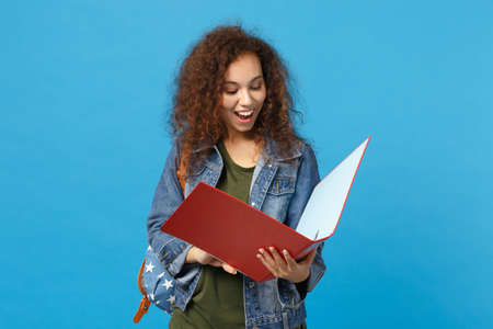 Young african american girl teen student in denim clothes backpack hold folder isolated on blue background studio portrait. Education in high school university college concept. Mock up copy space