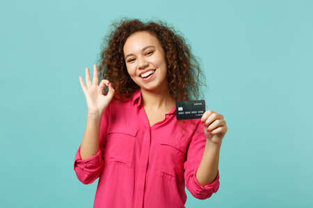Funny african girl in pink casual clothes showing OK gesture hold credit bank card isolated on blue turquoise wall background in studio. People sincere emotions, lifestyle concept. Mock up copy space