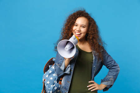 Young african american girl teen student in denim clothes, backpack hold megaphone isolated on blue background studio portrait. Education in high school university college concept. Mock up copy space 免版税图像