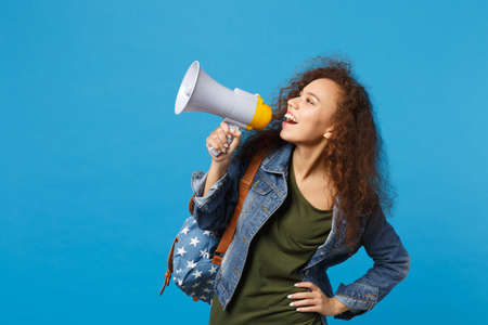 Young african american girl teen student in denim clothes, backpack hold megaphone isolated on blue background studio portrait. Education in high school university college concept. Mock up copy space Archivio Fotografico