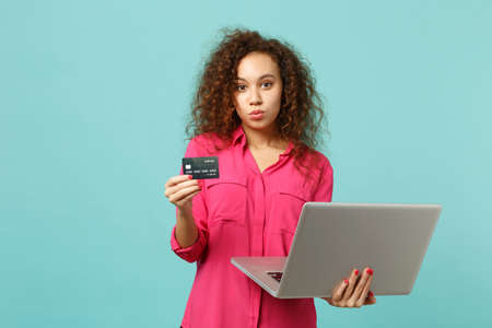 Beautiful african girl in casual clothes using laptop computer holding credit bank card isolated on blue turquoise background in studio. People sincere emotions lifestyle concept. Mock up copy space