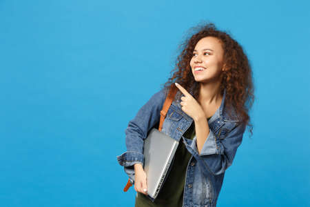 Young african american girl teen student in denim clothes, backpack hold pc isolated on blue wall background studio portrait. Education in high school university college concept. Mock up copy space Stockfoto
