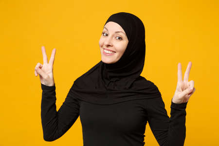Smiling beautiful young arabian muslim woman in hijab black clothes showing victory sign isolated on yellow background, studio portrait. People religious Islam lifestyle concept. Mock up copy space