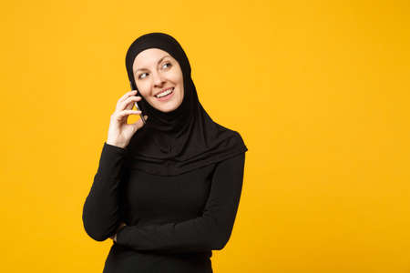 Smiling young arabian muslim woman in hijab black clothes hold in hands talking on mobile phone isolated on yellow background, studio portrait. People religious lifestyle concept. Mock up copy space