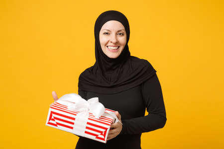Smiling young arabian muslim woman in hijab black clothes hold in hand present box with gift isolated on yellow wall background studio portrait. People religious lifestyle concept. Mock up copy space Imagens