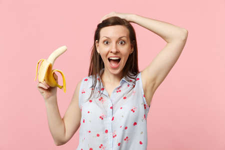 Excited young woman in summer clothes keeping mouth open, holding fresh ripe banana fruit isolated on pink pastel wall background. People vivid lifestyle, relax vacation concept. Mock up copy space