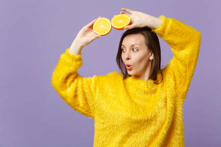 Amazed young woman in fur sweater looking aside hold in hands halfs of fresh ripe orange fruit isolated on violet pastel background. People vivid lifestyle relax vacation concept. Mock up copy space Imagens