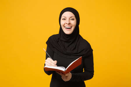 Young arabian muslim woman in hijab black clothes hold notebook, writing, prepare to exam isolated on yellow wall background, studio portrait. People religious lifestyle concept. Mock up copy space Stok Fotoğraf