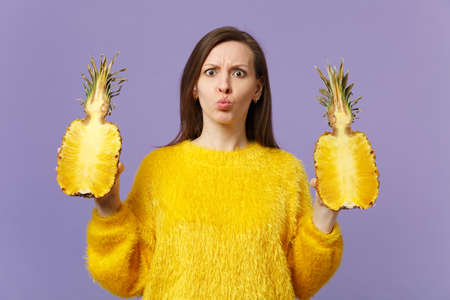 Puzzled young girl in fur sweater blowing lips holding halfs of fresh ripe pineapple fruit isolated on violet pastel wall background. People vivid lifestyle relax vacation concept. Mock up copy space