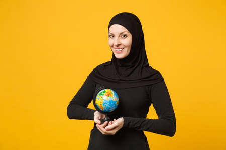 Young arabian muslim student girl in hijab black clothes hold in hands Earth world globe isolated on yellow wall background, studio portrait. People religious lifestyle concept. Mock up copy space Stock Photo