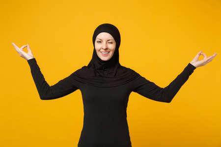 La giovane donna musulmana araba in abiti neri hijab si tiene per mano nel gesto di yoga, si rilassa meditando isolato su sfondo giallo, ritratto in studio. Concetto di stile di vita religioso della gente. Mock up copia spazio Archivio Fotografico