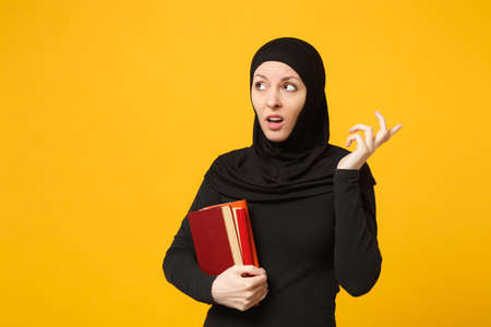 Arabian muslim student girl in hijab black clothes holds books isolated on yellow wall background, studio portrait. People religious lifestyle, education in high school concept. Mock up copy space Фото со стока