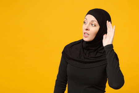Sad crying confused young arabian muslim woman in hijab black clothes try to hear you isolated on yellow wall background, studio portrait. People religious Islam lifestyle concept. Mock up copy space Reklamní fotografie