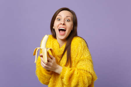 Surprised young woman in fur sweater keeping mouth open holding in hand fresh ripe banana fruit isolated on violet pastel background. People vivid lifestyle relax vacation concept. Mock up copy space