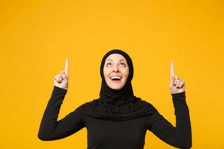 Smiling young arabian muslim woman in hijab black clothes showing pointing copy space with hands finger isolated on yellow background, studio portrait. People religious lifestyle concept. Mock up