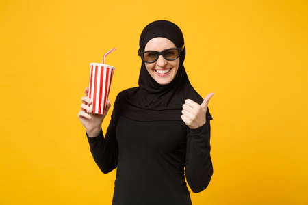 Arabian muslim woman in hijab black clothes 3d imax glasses watch movie film hold paper cup of soda isolated on yellow wall background studio portrait. People lifestyle concept. Mock up copy space