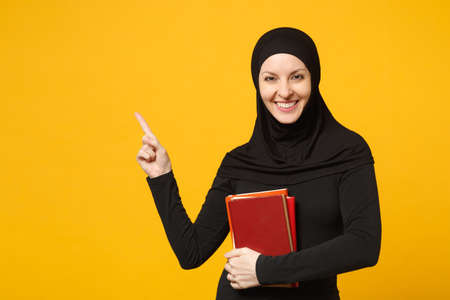 Arabian muslim student girl in hijab black clothes holds books isolated on yellow wall background, studio portrait. People religious lifestyle, education in high school concept. Mock up copy space Reklamní fotografie