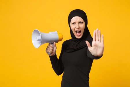 Young arabian muslim woman in hijab black clothes holds in hand bullhorn public address megaphone isolated on yellow background studio portrait. People religious lifestyle concept. Mock up copy space