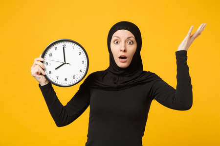 Young arabian muslim woman in hijab black clothes hold in hands round clock isolated on yellow wall background studio portrait. People religious lifestyle, time management concept. Mock up copy space
