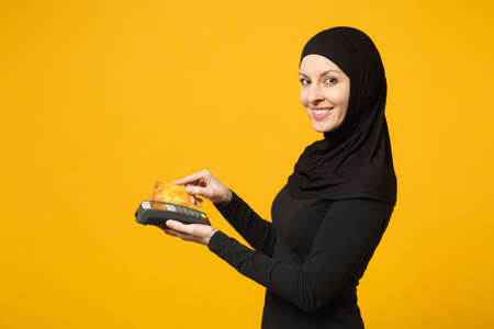 Arabian muslim woman in hijab black clothes hold payment terminal to process and acquire credit card payments isolated on yellow background. People religious lifestyle concept. Mock up copy space