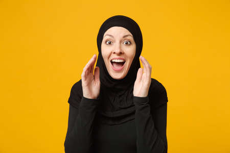 Smiling young arabian muslim woman in hijab black clothes whispering secret behind her hand isolated on yellow wall background, studio portrait. People religious lifestyle concept. Mock up copy space