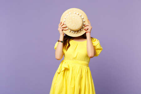 Portrait of young woman in yellow dress covering face with summer hat isolated on pastel violet background in studio. People sincere emotions, lifestyle concept. Mock up copy space. Advertising area