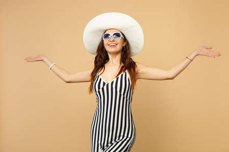 Smiling young woman in black and white striped dress, hat and sunglasses spreading hands isolated on pastel beige background in studio. People sincere emotions, lifestyle concept. Mock up copy space Фото со стока