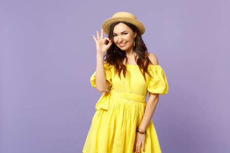 Portrait of stunning young woman in yellow dress, summer hat showing OK gesture looking camera isolated on pastel violet wall background. People sincere emotions lifestyle concept. Mock up copy space