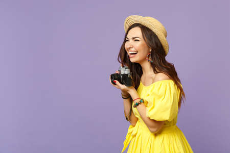 Laughing young woman in yellow dress hat taking picture on retro vintage photo camera looking aside isolated on pastel violet background. People sincere emotions lifestyle concept. Mock up copy space