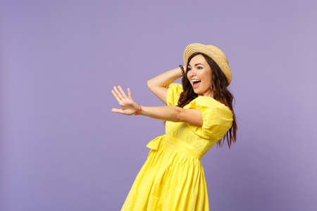 Excited young woman in yellow dress, summer hat waving, greeting with hand as notices someone isolated on pastel violet wall background. People sincere emotions, lifestyle concept. Mock up copy space