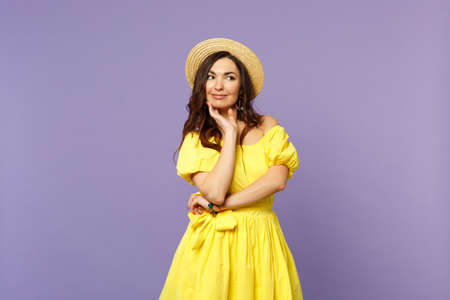 Portrait of pensive young woman in yellow dress, summer hat looking aside, put hand prop up on chin isolated on pastel violet background. People sincere emotions lifestyle concept. Mock up copy space