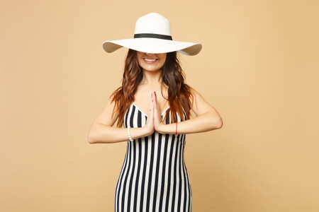 Smiling woman in black and white striped dress covering eyes with hat folded hands praying meditating isolated on pastel beige background. People sincere emotion lifestyle concept. Mock up copy space