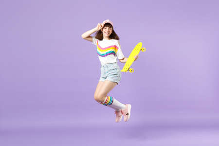 Portrait of smiling teen girl in vivid clothes holding yellow skateboard, having fun, jumping isolated on violet pastel wall background. People sincere emotions, lifestyle concept. Mock up copy space