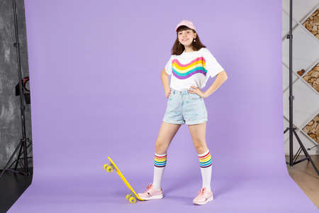 Smiling teen girl in vivid clothes standing with arms akimbo with yellow skateboard isolated on violet pastel wall background in studio. People sincere emotions, lifestyle concept. Mock up copy space