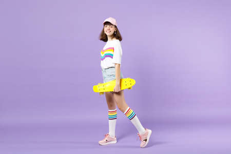 Side view of funny teen girl in vivid clothes holding yellow skateboard, looking camera isolated on violet pastel background in studio. People sincere emotions, lifestyle concept. Mock up copy space 版權商用圖片