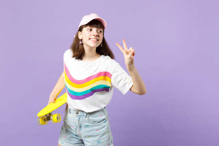 Charming teen girl in vivid clothes looking aside, holding yellow skateboard, showing victory sign isolated on violet pastel background. People sincere emotions, lifestyle concept. Mock up copy space