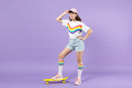 Pretty teen girl in vivid clothes standing with yellow skateboard blowing bubble gum isolated on violet pastel wall background in studio. People sincere emotions lifestyle concept. Mock up copy space 免版税图像
