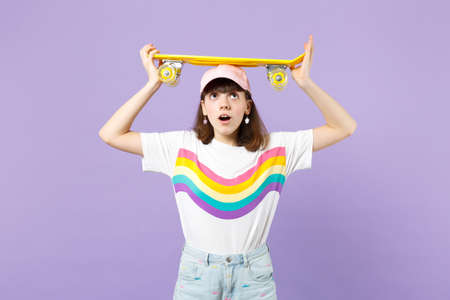 Amazed teen girl in vivid clothes holding yellow skateboard on head, keeping mouth open looking up isolated on violet pastel background. People sincere emotions, lifestyle concept. Mock up copy space