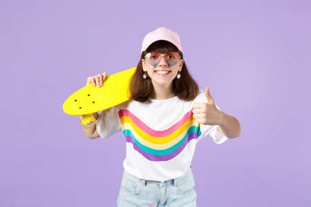 Joyful teen girl in vivid clothes, heart eyeglasses hold yellow skateboard, showing thumb up isolated on violet pastel wall background. People sincere emotions, lifestyle concept. Mock up copy space