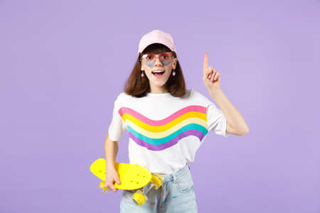 Excited teen girl in vivid clothes, eyeglasses with skateboard holding index finger up with great new idea isolated on violet background. People sincere emotions lifestyle concept. Mock up copy space