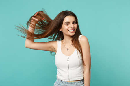 Portrait of smiling young woman in light casual clothes looking camera holding hair isolated on blue turquoise wall background in studio. People sincere emotions lifestyle concept. Mock up copy space Фото со стока