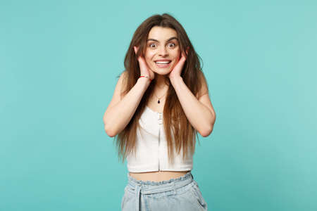 Excited smiling young woman in light casual clothes looking camera, putting hands on face isolated on blue turquoise wall background. People sincere emotions, lifestyle concept. Mock up copy space