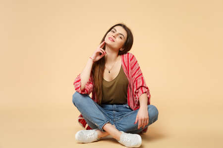 Portrait of smiling stunning young woman in casual clothes sitting, looking camera isolated on pastel beige wall background in studio. People sincere emotions, lifestyle concept. Mock up copy space Фото со стока