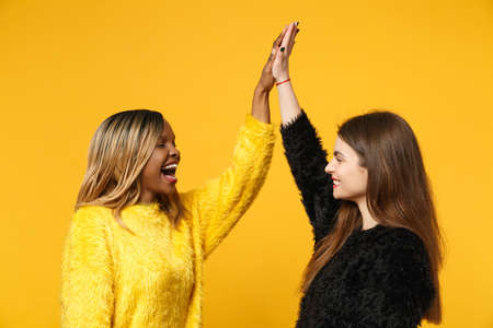 Two young women friends european and african american in black yellow clothes standing posing isolated on bright orange wall background, studio portrait. People lifestyle concept. Mock up copy space