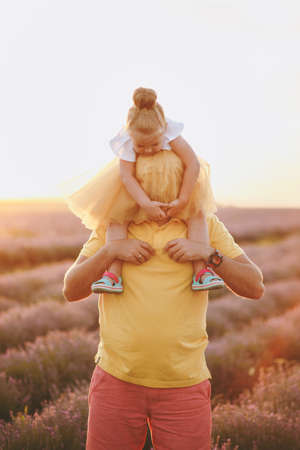 Young family in yellow clothes walk on purple lavender flower meadow field background, have fun, play with little cute child baby girl. Father hold on neck kid daughter. Outdoors summer day concept