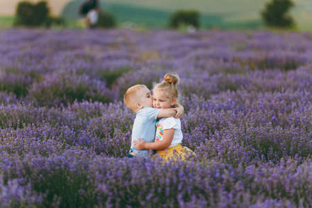 Playful little cute couple boy girl walk on purple lavender flower meadow field background, have fun, play, enjoy good sunny day. Excited small kids. Family day, children, childhood lifestyle concept Banque d'images - 122167790