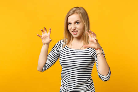 Funny young woman in striped clothes shouting, growling like animal, making cat claws gesture isolated on yellow orange wall background. People sincere emotions, lifestyle concept. Mock up copy space