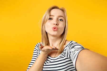 Close up selfie shot of tender young woman in striped clothes blowing sending air kiss isolated on yellow orange background in studio. People sincere emotions, lifestyle concept. Mock up copy space 写真素材
